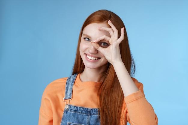Recherche fille perfection charmante jolie étudiante rousse heureuse assurant tout ok montrant ok signe oeil à travers sourire ravi express attitude positive fond bleu
