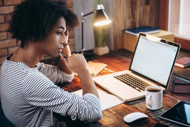 Recherche d'inspiration. vue latérale d'un jeune homme africain tenant la main sur le menton et regardant ailleurs alors qu'il était assis sur son lieu de travail