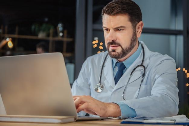 Recherche sur internet. bel homme beau intelligent assis à l'ordinateur portable et se concentrant sur son travail tout en faisant une recherche sur internet