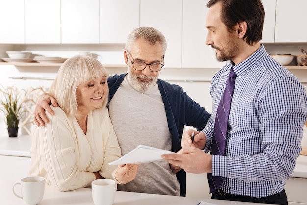 À la recherche d'un investissement financier réussi. les propriétaires de couples de personnes âgées curieux, ravis, amicaux, rencontrent un conseiller financier et le consultent lors du choix de la variante d'investissement