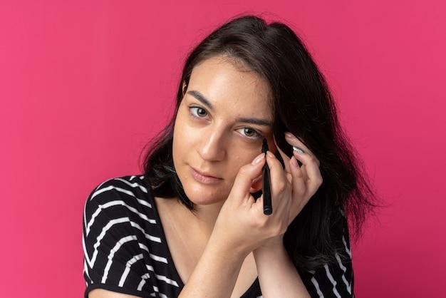 À la recherche d'une jeune fille belle dessiner une flèche avec un eye-liner isolé sur un mur rose