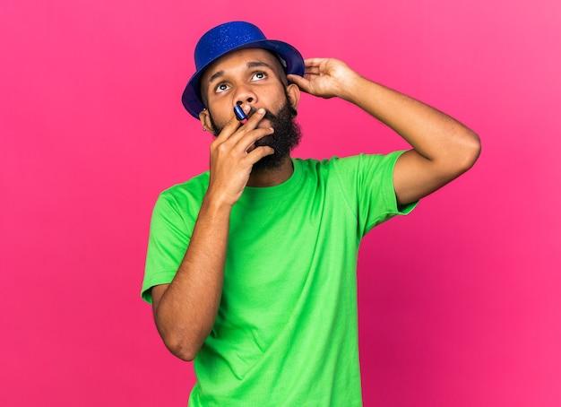 À la recherche d'un jeune homme afro-américain portant un chapeau de fête soufflant un sifflet de fête