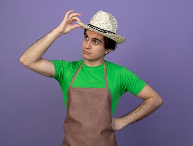 À la recherche de jeunes hommes jardinier en uniforme portant chapeau de jardinage holding hat mettre la main sur la hanche
