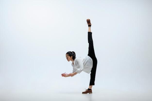 À la recherche des meilleures chances de la journée. heureuse femme travaillant au bureau, sauter et danser dans des vêtements décontractés ou costume isolé sur fond de studio blanc. entreprise, start-up, concept d'espace ouvert de travail.