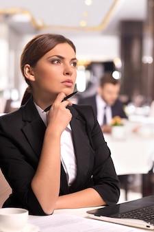 A la recherche de nouvelles idées commerciales. une jeune femme réfléchie en tenue de soirée tenant la main sur le menton et regardant ailleurs alors qu'elle était assise au restaurant