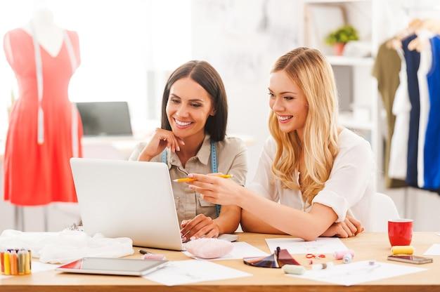 Recherche des nouvelles tendances de la mode. deux jeunes femmes joyeuses travaillant ensemble assises au bureau de leur atelier de mode