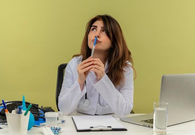 À la recherche de la pensée à la femme médecin d'âge moyen portant une robe médicale avec stéthoscope assis au bureau de travail sur un ordinateur portable avec des outils médicaux mettant un stylo sur la bouche sur un mur vert avec espace de copie