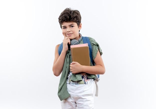 À la recherche d'un petit écolier portant un sac à dos et un casque tenant un livre et mettant le doigt sur la joue
