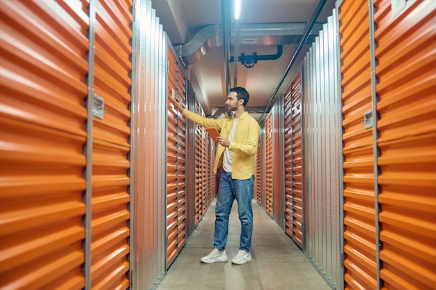 Recherche réussie. jeune homme satisfait barbu de profil avec tablette touchant la porte du conteneur souhaité dans un entrepôt moderne