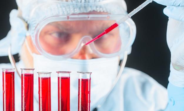 Recherche sur le sang. le médecin travaille avec un échantillon de sang. prise de sang en laboratoire. équipement médical. fermer.