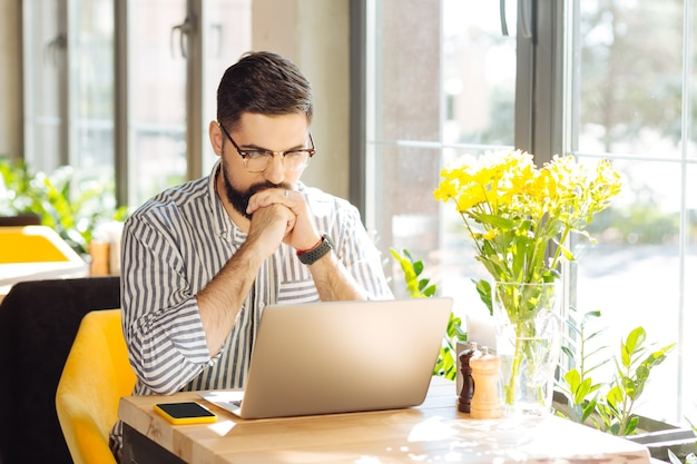 A la recherche d'une solution. homme sérieux et réfléchi regardant l'écran de l'ordinateur portable tout en pensant à la solution au problème