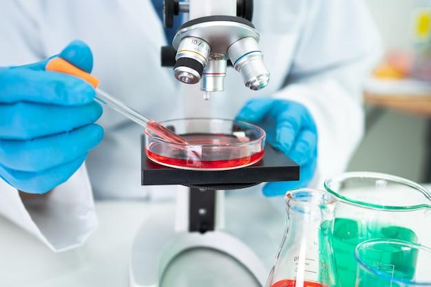 Recherche de travail de biochimiste scientifique asiatique avec un microscope en laboratoire