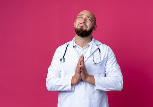 À la recherche de triste jeune médecin de sexe masculin portant une robe médicale et un stéthoscope montrant le geste de prier isolé sur un mur rose