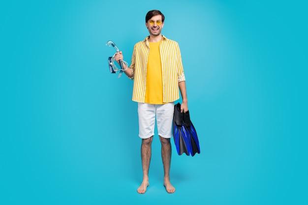 Récif de corail j'y vais. photo pleine grandeur voyageur positif gars tenir équipement de plongée palmes masque lunettes tube porter chemise rayée jaune short blanc pieds nus isolé fond de couleur bleu