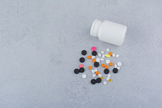 Récipient blanc et tas de diverses pilules sur une surface en marbre.
