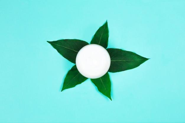 Récipient de crème cosmétique avec des feuilles vertes. crème pour le corps