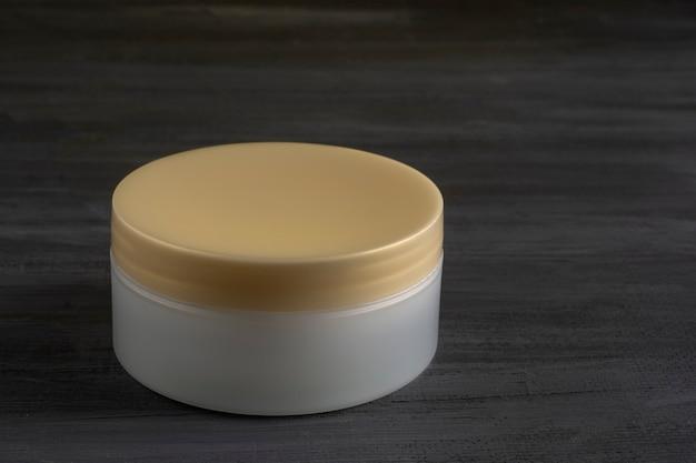 Récipient à crème avec un couvercle doré et un fond en bois noir