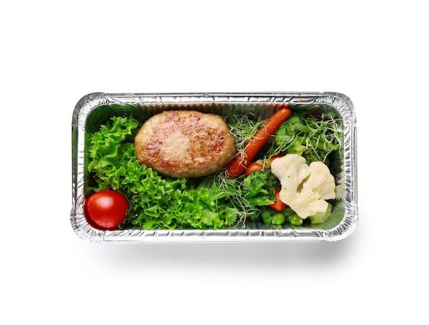 Récipient avec de délicieux plats pour la livraison sur une surface blanche