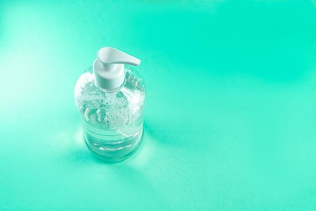 Récipient avec gel d'alcool sur le mur bleu clair