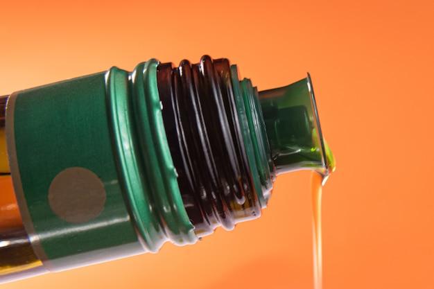 Récipient d'huile d'olive sur fond orange