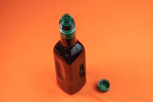 Récipient d'huile d'olive sur une surface orange