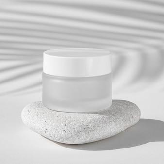 Récipient d'hydratation de soins de la peau sur un rocher blanc