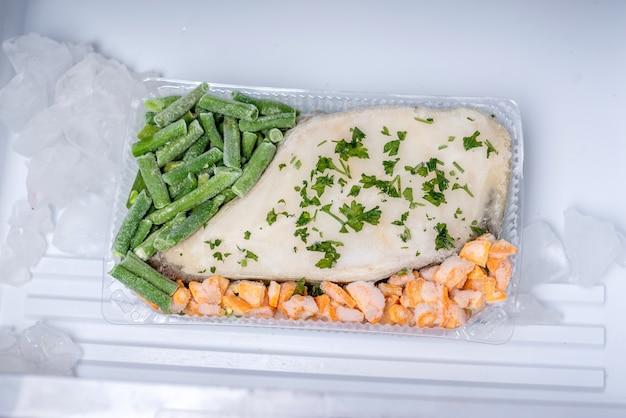 Récipient avec des légumes surgelés et du poisson dans le congélateur du réfrigérateur