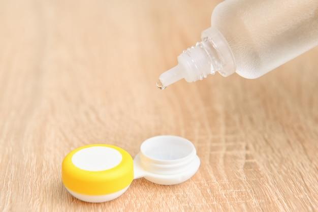 Récipient avec lentilles de contact et solution sur table en bois