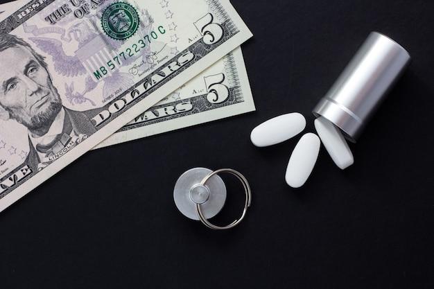 Récipient en métal pour les pilules et de l'argent sur un fond noir, concept de médicaments coûteux, clo