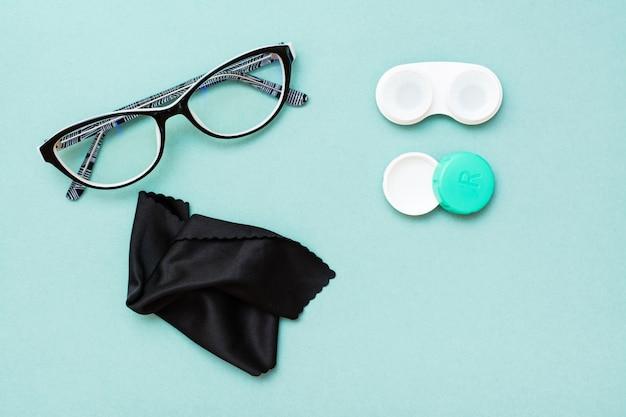 Récipient ouvert avec lentilles, lunettes et chiffon de nettoyage