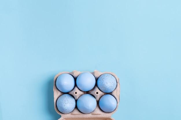 Récipient en papier avec des oeufs de pâques bleu pastel peints à la main