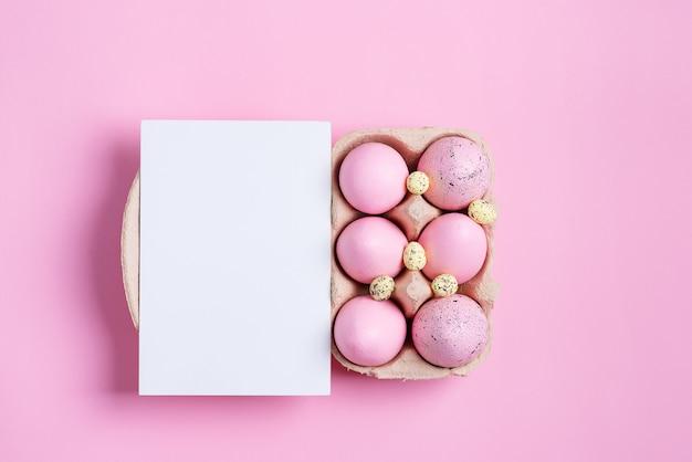 Récipient en papier avec des oeufs de pâques roses pastel peints à la main et une feuille de papier blanc