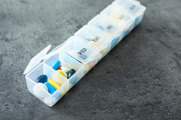 Récipient en plastique avec différentes pilules sur table grise