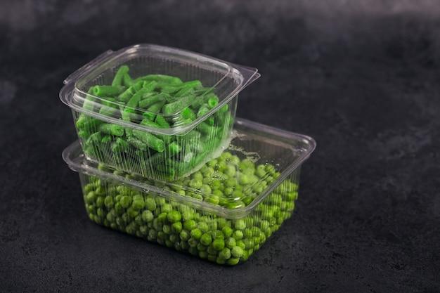 Récipient en plastique avec différents légumes bio surgelés sur un tableau noir