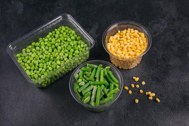 Récipient en plastique avec différents légumes surgelés biologiques sur une table noire. pois verts, maïs sucré et haricots verts coupés dans une boîte