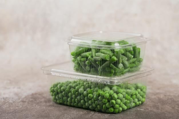 Récipient en plastique avec différents légumes surgelés biologiques sur une table. pois verts et haricots verts coupés dans une boîte
