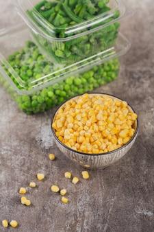 Récipient en plastique avec différents légumes surgelés biologiques sur une table. pois verts, maïs sucré et haricots verts coupés dans une boîte