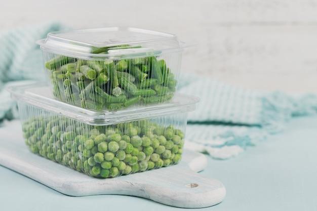 Récipient en plastique avec des légumes surgelés biologiques sur une table. pois verts et haricots verts coupés dans une boîte