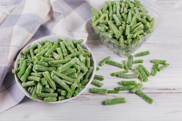 Récipient en plastique avec des légumes surgelés biologiques sur un tableau blanc. couper les haricots verts dans une boîte