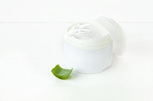 Récipient en plastique ouvert avec de la crème et de l'aloès