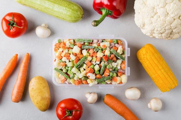 Récipient en plastique rectangulaire avec mélange de légumes surgelés à plat sur fond gris avec des aliments frais