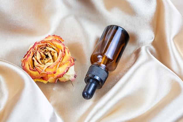 Un récipient pour ranger les produits cosmétiques en verre foncé repose sur les plis du tissu en satin de soie, entouré de fleurs roses séchées. flacon de parfum, sérum ou lotion