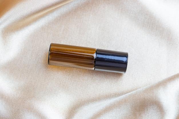 Un récipient pour stocker des produits cosmétiques en verre foncé repose sur les plis d'un tissu en satin de soie. flacon de parfum, sérum ou lotion