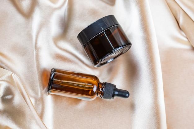 Un récipient pour stocker des produits cosmétiques en verre foncé repose sur les plis d'un tissu en satin de soie. parfum produit de beauté cosmétique.