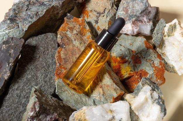 Un récipient en verre transparent avec de l'huile naturelle pour le corps et les cheveux repose sur les pierres. cosmétiques naturels et bio. concept de cosmétologie et de beauté.