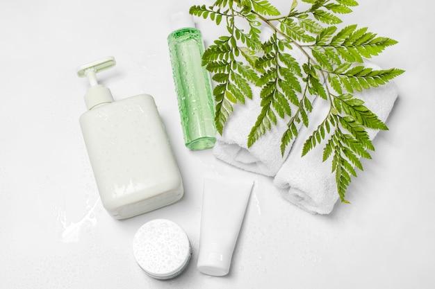Récipients cosmétiques avec des feuilles à base de plantes vertes et des gouttes d'eau, emballage d'étiquette vierge pour la maquette de marque. crème hydratante, shampooing, tonique, soin du visage et du corps.