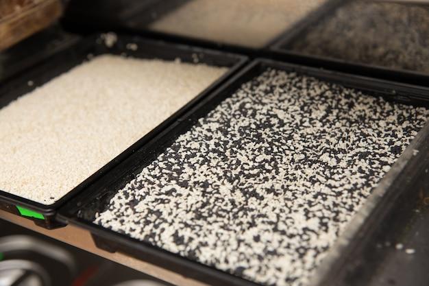 Récipients en plastique avec des graines de sésame blanches et noires
