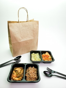 Récipients en plastique avec de la nourriture délicieuse et un sac en papier sur la table. service de livraison