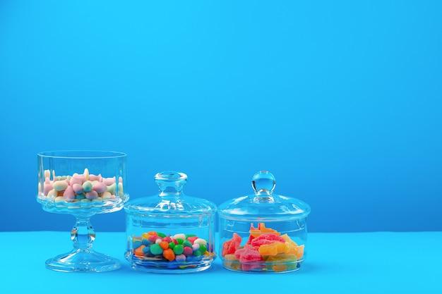 Récipients en verre avec des bonbons colorés contre le bleu