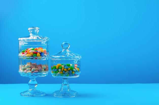 Récipients en verre avec des bonbons colorés sur fond bleu